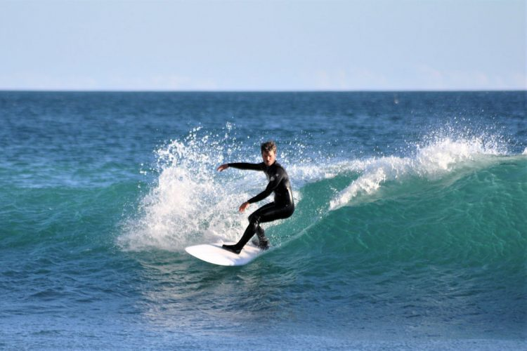 Great surf conditions as a surfer rides a wave at Black Rock