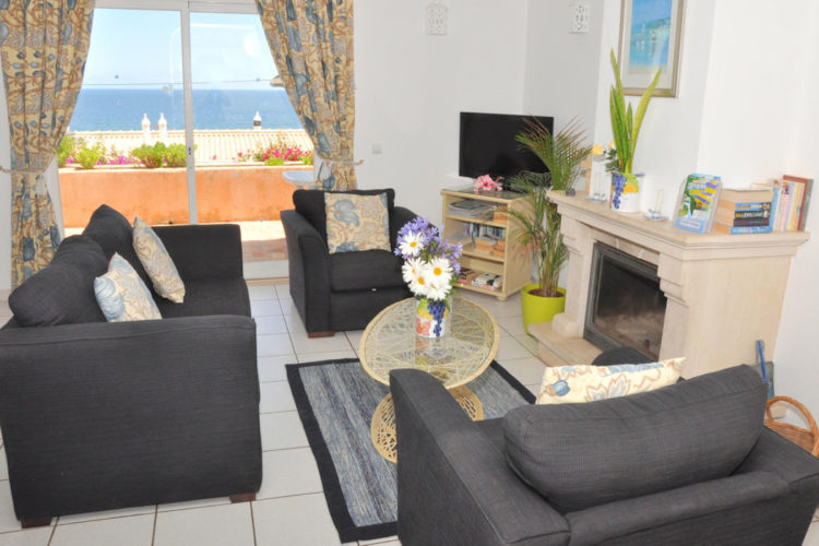 Ocean Villas Luz one bedroom apartments offer an open plan lounge with sofa and fireplace and spectacular sea views