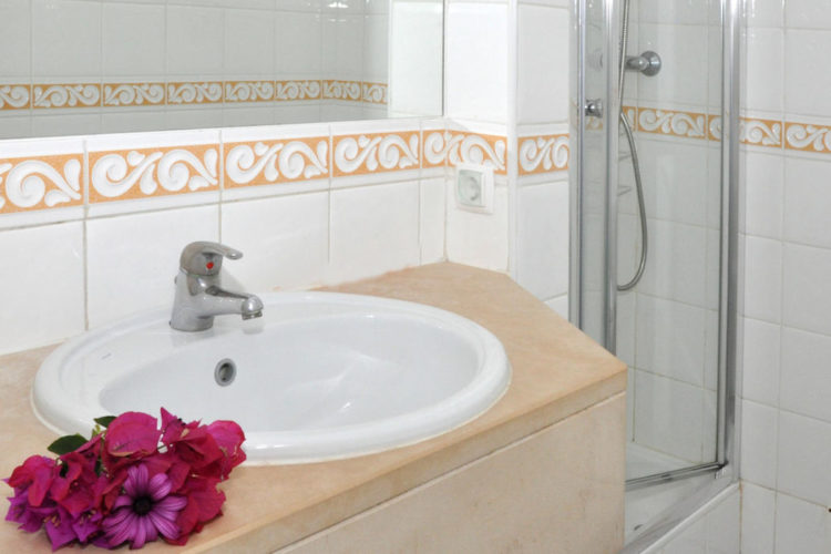 Pretty pink flowers on the sink in one of the two bathrooms at Ocean Villas Luz